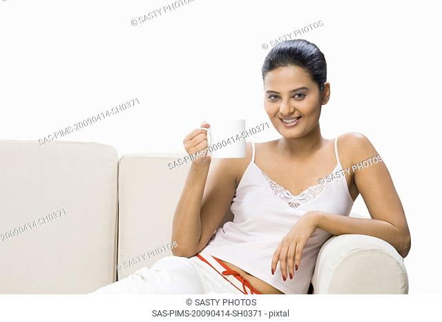 Woman enjoying a cup of coffee on a couch