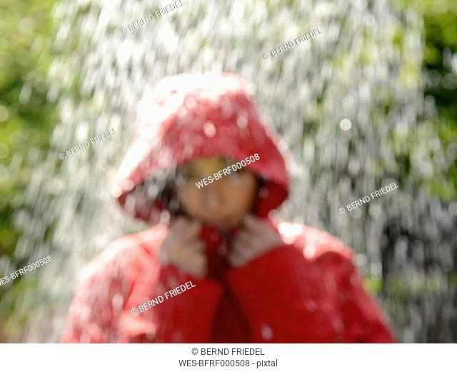 Blurred portrait of young woman wearing red hooded jacket standing in the rain