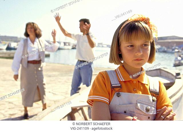 portrait, girl with short blond hair, 10 years, wearing orange polo-shirt sits sad in a wall, whiles her parents are quarreling on the quay  - GERMANY