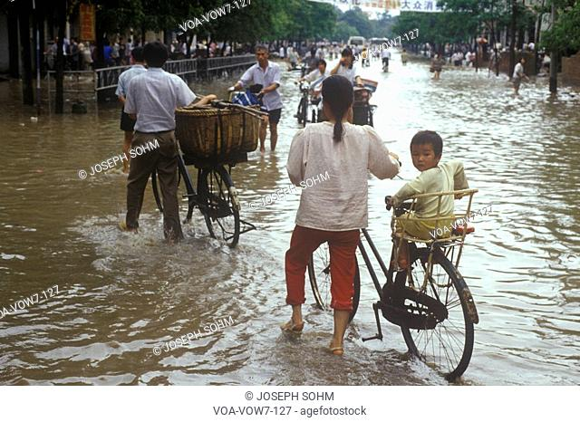 People trying to cross flooded road near Li River in Guilin, Guangxi Province, People's Republic of China