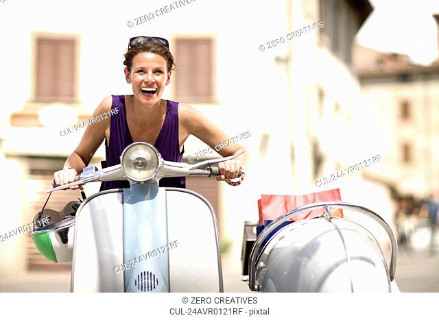 Woman driving a vespa