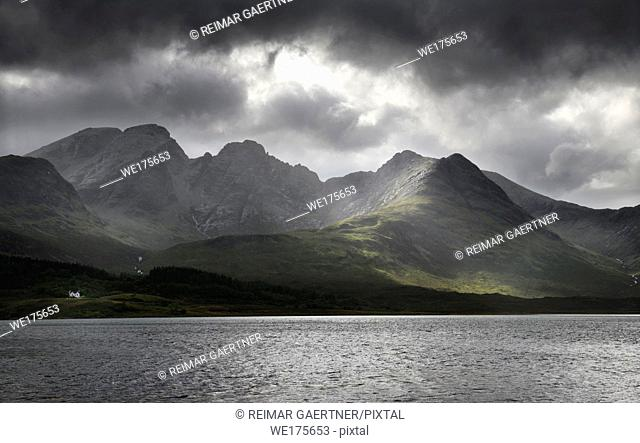 White house under Blaven mountains of Black Cuillin Hills with sun rays under dark clouds at Loch Slapin Isle of Skye Scotland UK