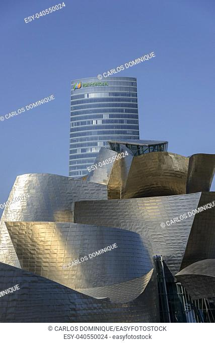 Guggenheim Bilbao museum with office building at back on a sunny day
