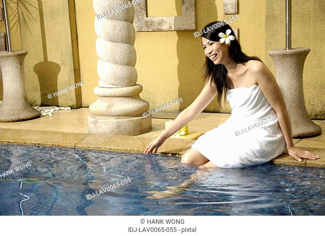 Woman putting her legs in a swimming pool and smiling
