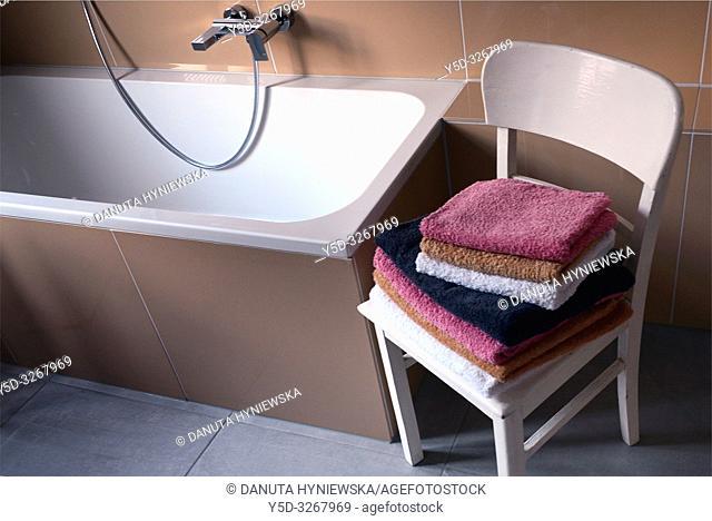 Interior scene, bathroom, stack of folded towels on vintage white chair near bathtub