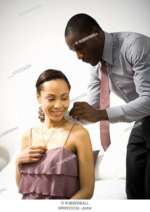 Man doing up a womans necklace clasp