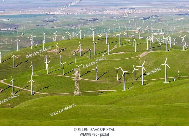 Many windmills in a large hilly field overlooking the town of Livermore, California