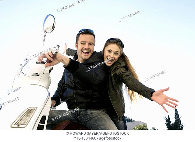 Couple sitting on a motor scooter and cheering