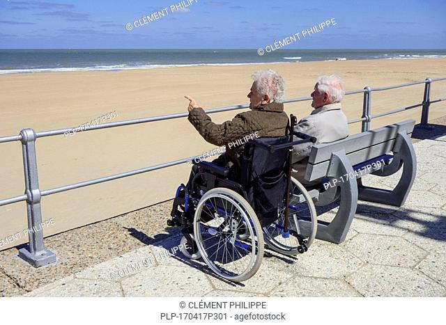 Disabled elderly woman in wheelchair and retired husband sitting on a bench at promenade along the coast on a cold sunny day in spring