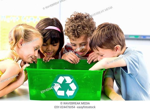 Children looking at plastic bottles in recycling box
