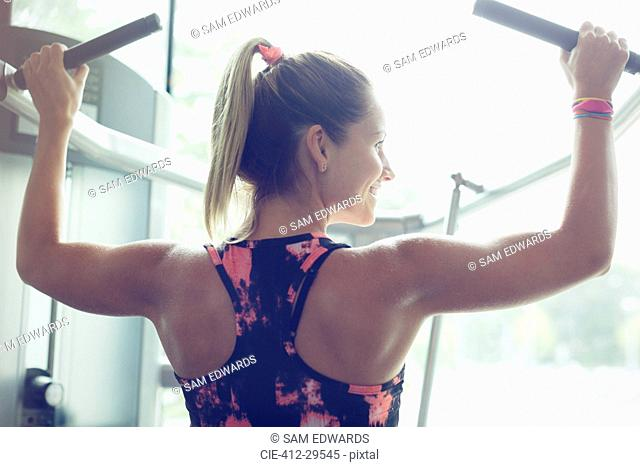 Fit woman doing lat pulldowns on equipment at gym