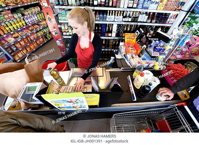 A cashier scans goods and food with clients in a supermarket