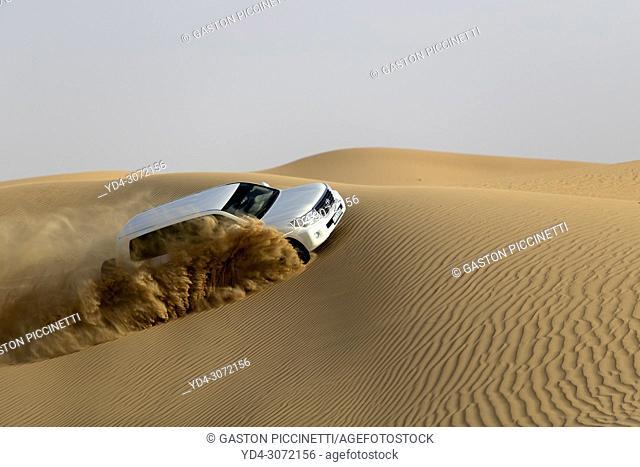 Off road vehicle driving over desert dunes, Dubai, United Arab Emirates
