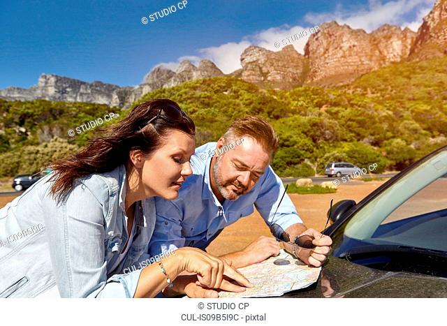 Couple leaning on car bonnet, looking at map, Cape town