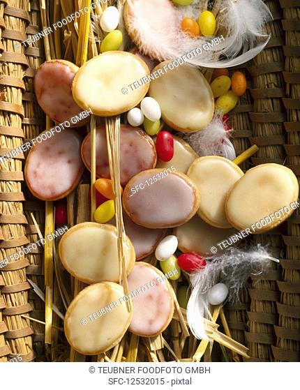 Glazed lemon and raspberry cookies in a woven basket with feathers for Easter