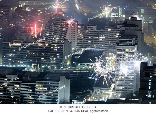 01 January 2019, Bavaria, München: Fireworks rockets explode on New Year's Eve from 31.12.2018 to 01.01.2019 between residential buildings
