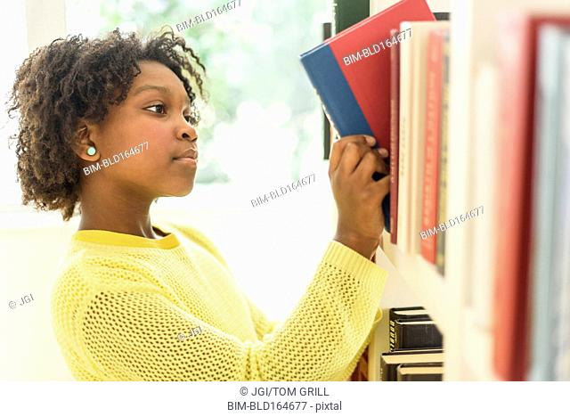 Black student choosing book from library shelf