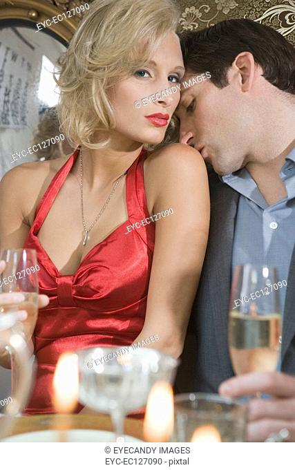 Portrait of sexy couple at Christmas dinner party, man kissing woman's shoulder