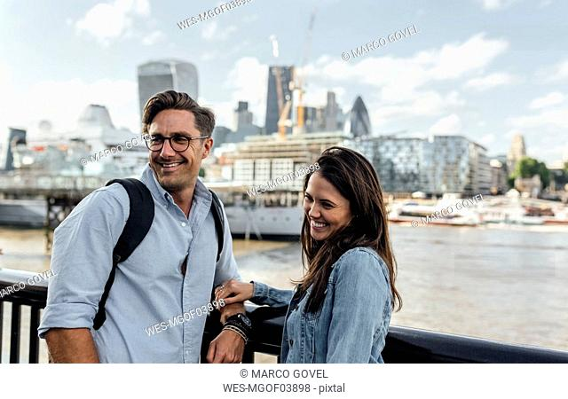 UK, London, smiling couple with skyline in the background