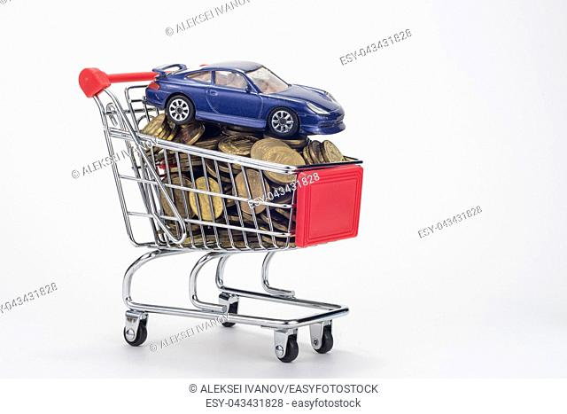 A grocery shopping cart filled with coins and a car on top