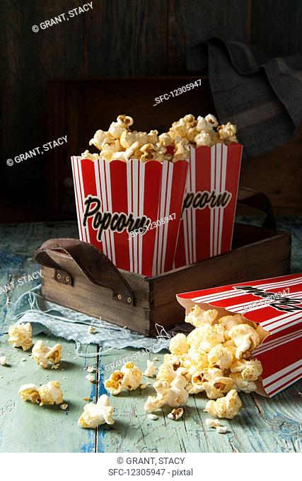 Two red and white striped boxes of popcorn on a wooden tray one box tipped over with popcorn spilling out onto an aqua green blue wooden surface