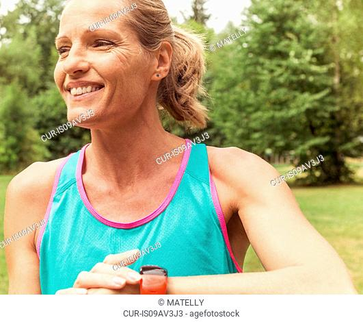 Mature woman, working out, outdoors, smiling