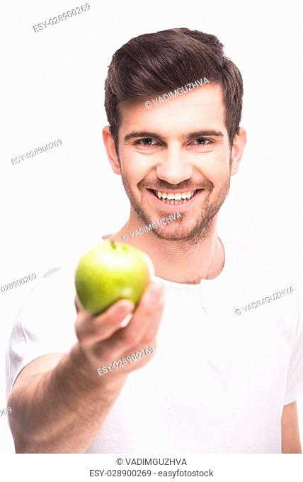 Handsome young man is holding a green apple, standing against white background