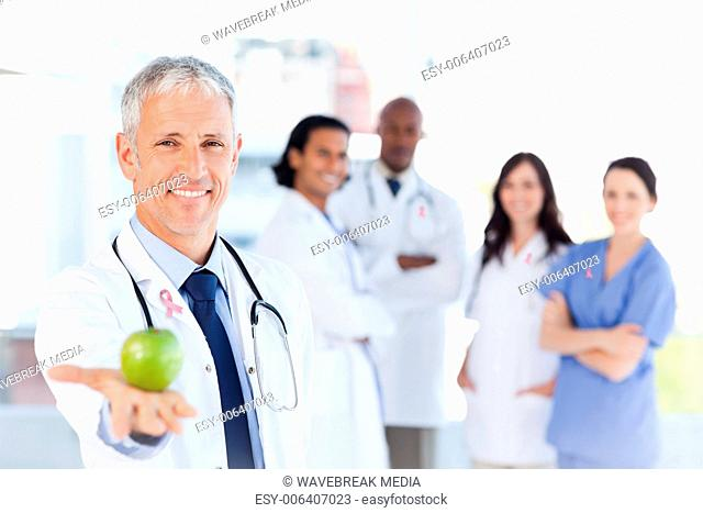 Composite image of mature doctor holding an apple