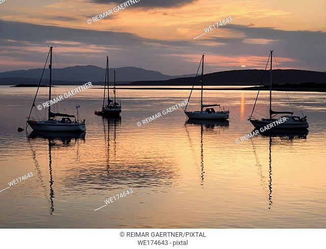 Red sky and clouds at sunset reflecting on the water of Ardmucknish Bay at North Connel with sailboats and Lismore island in silhouette