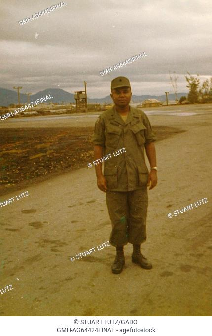 A full length portrait of Army Lieutenant AL Walker, posing for a photo in a relaxed posture, in front of the helipad at Danang Support Command, Vietnam, 1964