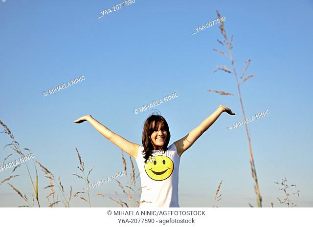 Happy young woman outdoors smiling arms outstretched