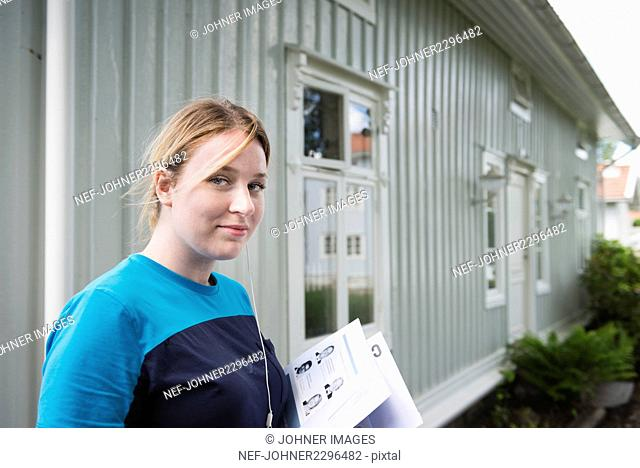 Portrait of young female mail carrier