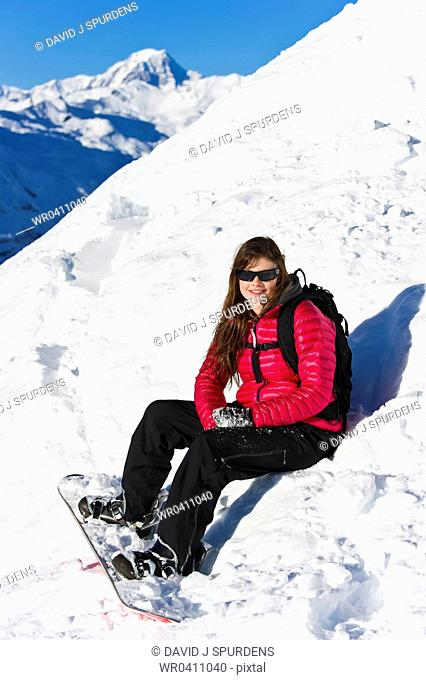 A female snowboarder sits in the fresh powder snow