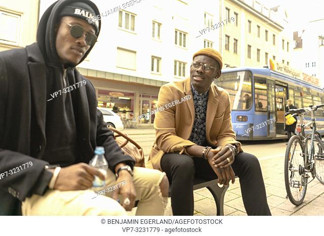 two fashionable male friends sitting together at bench at street in city Munich, Germany