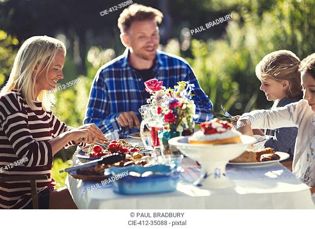 Family eating at sunny garden party patio table