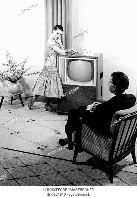 Woman posing in front of a TV set, man sitting in an armchair, historical photo, circa 1955
