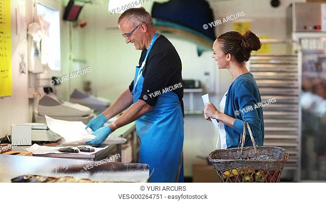 Friendly fishmonger sharing a joke with a female customer as he is wrapping up her choice of fresh fish