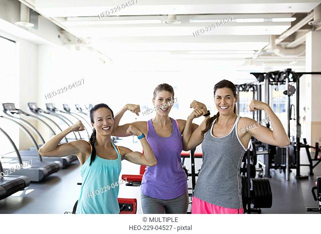 Portrait confident women flexing muscles at gym