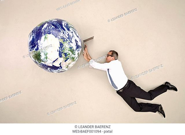 Businessman flying and working above the globe