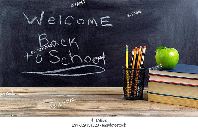 Old wooden desktop with basic school supplies and welcome back to school text on blackboard for students. Layout in horizontal format