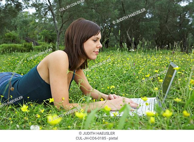 Young woman lying in meadow with laptop olive trees in background