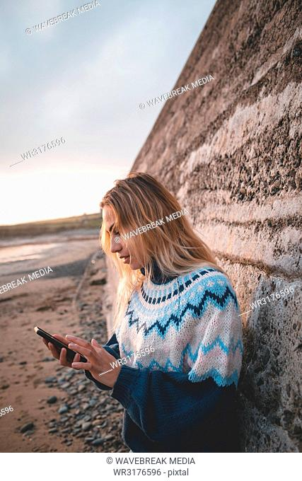 Woman using mobile phone on a beach