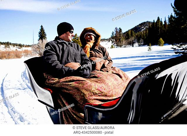friends sit under blankets in the winter, on snow filled sleigh ride