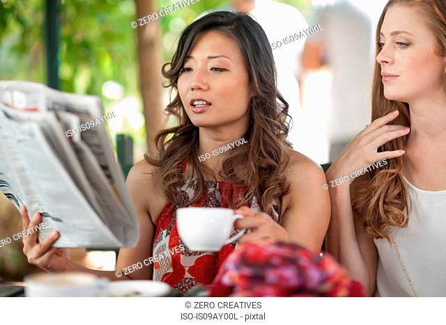 Two female friends reading newspaper at sidewalk cafe in city