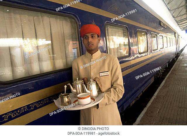 Rajasthani attendant holding tray of  beverage standing outside of Heritage on Wheels Journey into Past luxury tourist train ; Rajasthan ; India