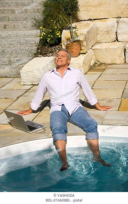 mature man enjoying the sun near swimming pool