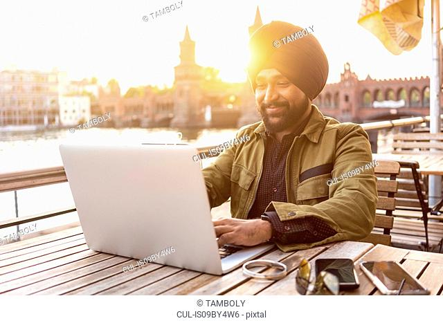 Indian man using laptop in cafe by river, Berlin, Germany