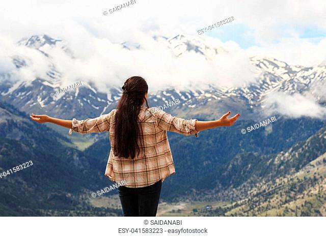 Backview portrait of traveller brunette woman with long straight hair wearing checked shirt and jeans enjoying picturesque panoramic view of mountains with snow...