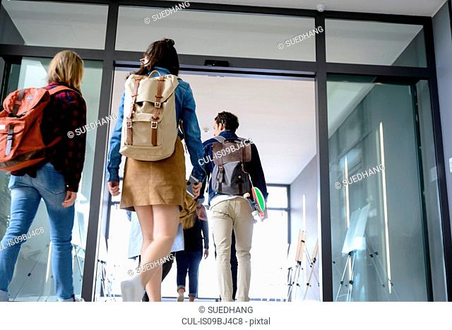 Students entering college building by glass doors