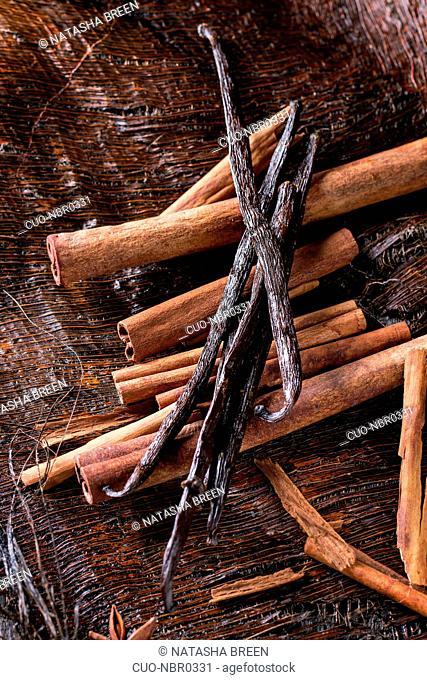 Heap of spices cinnamon sticks, vanilla sticks and anise stars over dark palm crust